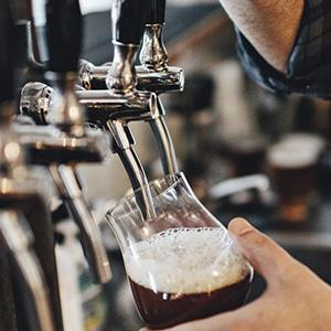 Close image of a person filling a beer stein from a tap