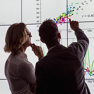 Two business professionals reviewing statistics on a board