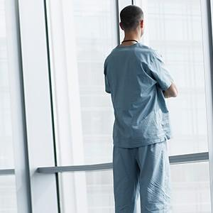 A healthcare professional looking out a window