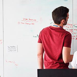 Man looking at whiteboard, facing away from camera
