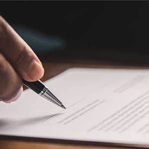 Signing a contract at a lawyer's desk
