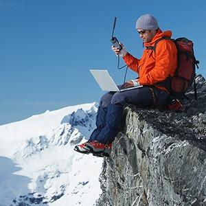 Man works from laptop in snowy mountain landscape