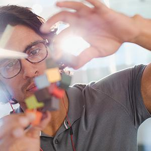 Close image of man with glasses tinkering with a small prototype