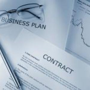 A contract, business plan, and market rates graphes with glasses and a pen.