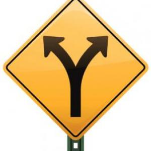 A yellow road sign with diverging arrows