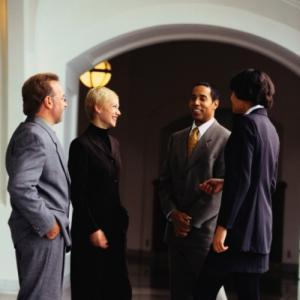 Four people in business suits standing together and talking